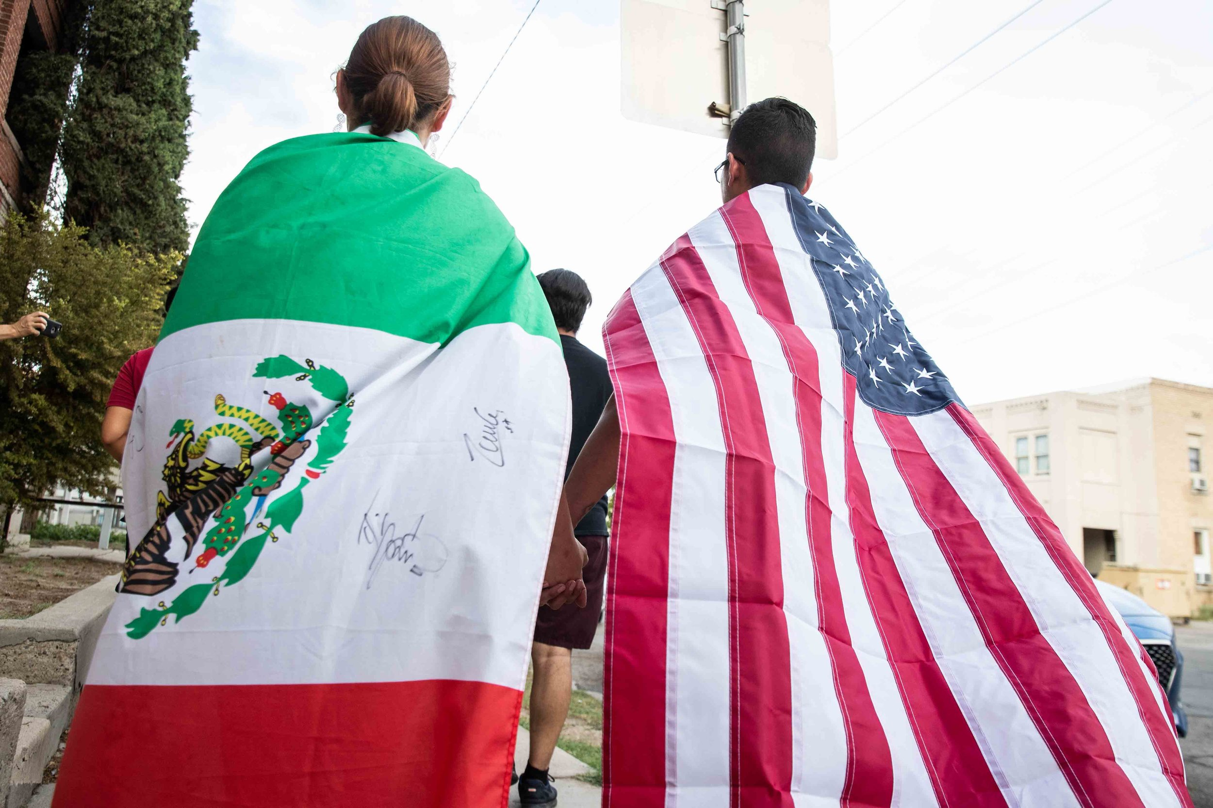 Samantha Ordaz (left) and Cesar Antonio Pacheco (right) carry the flags of Mexico and the United States as they walk holding hands during a silent march in honor to the victims of a mass shooting occurred in Walmart on Satuday morning in El Paso on Sunday, August 4, 2019.