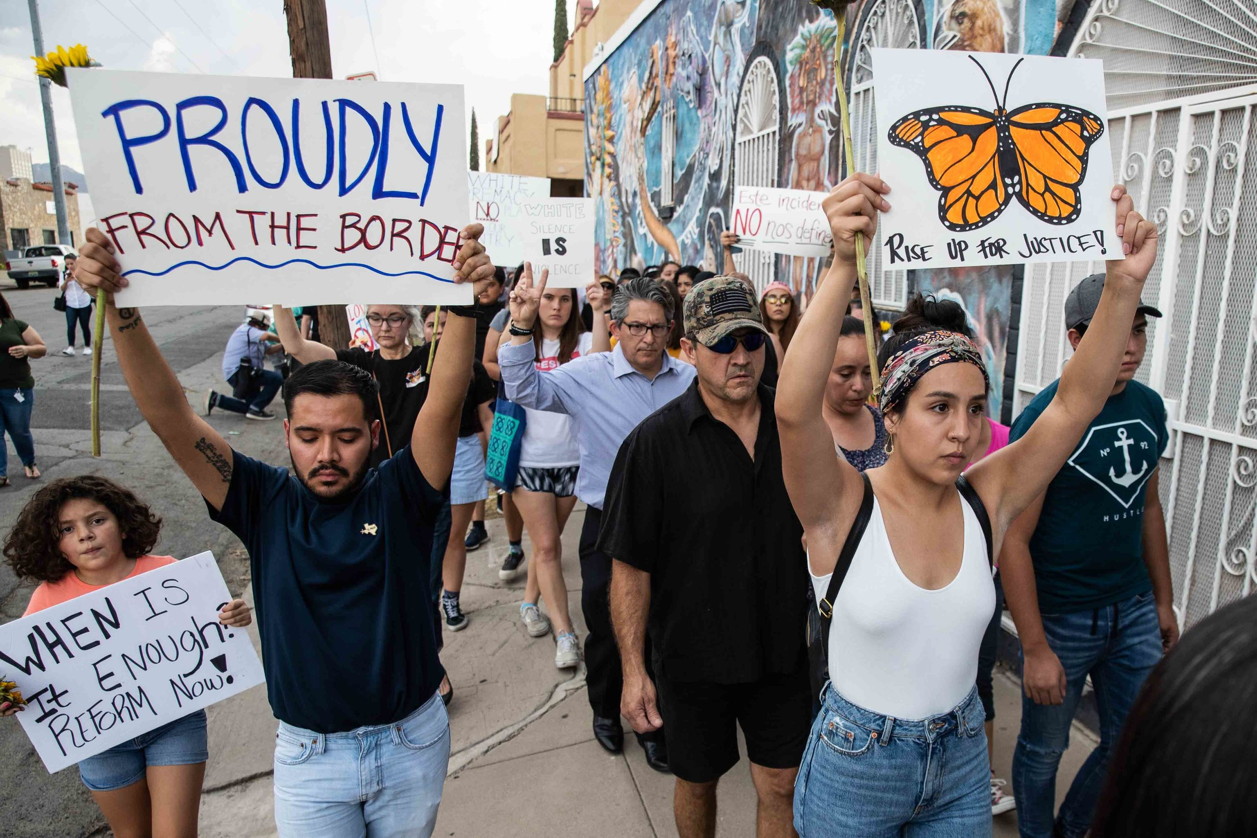 People march in silence holding sunflowers and sings in honor to the victims of a mass shooting occurred in Walmart on Satuday morning in El Paso on Sunday, August 4, 2019.
