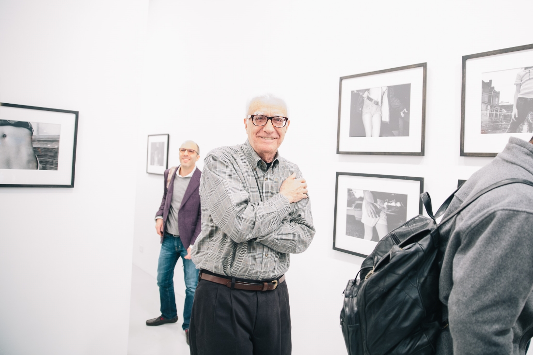 Mark Cohen, the artist, at his show May 10th. Ivan Shaw of Vogue in the background.