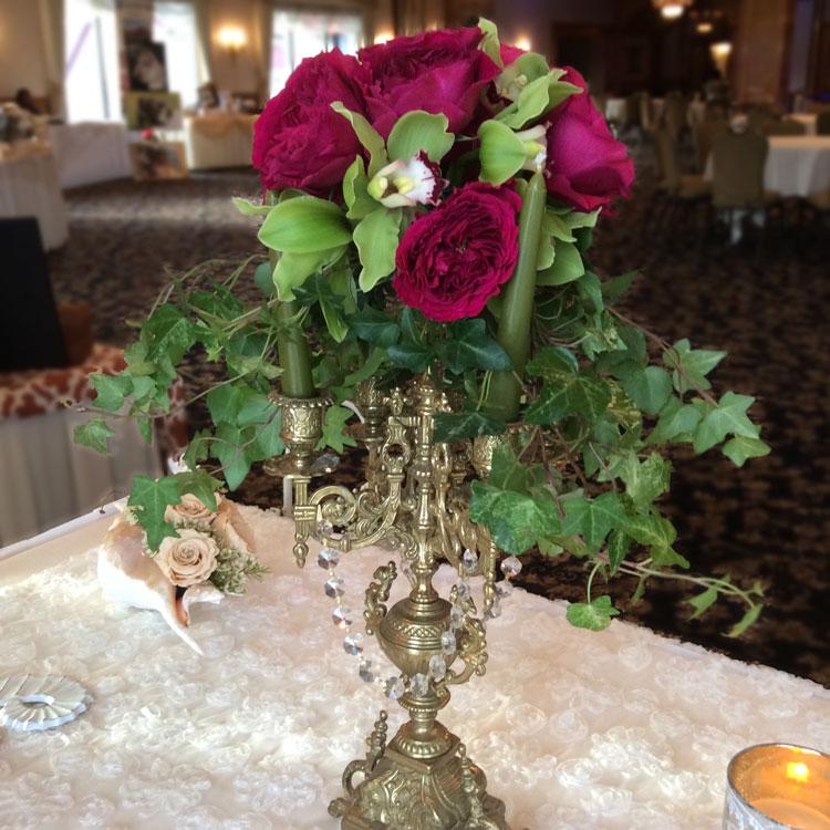 Candelabra centerpiece with cymbidium orchids & garden roses