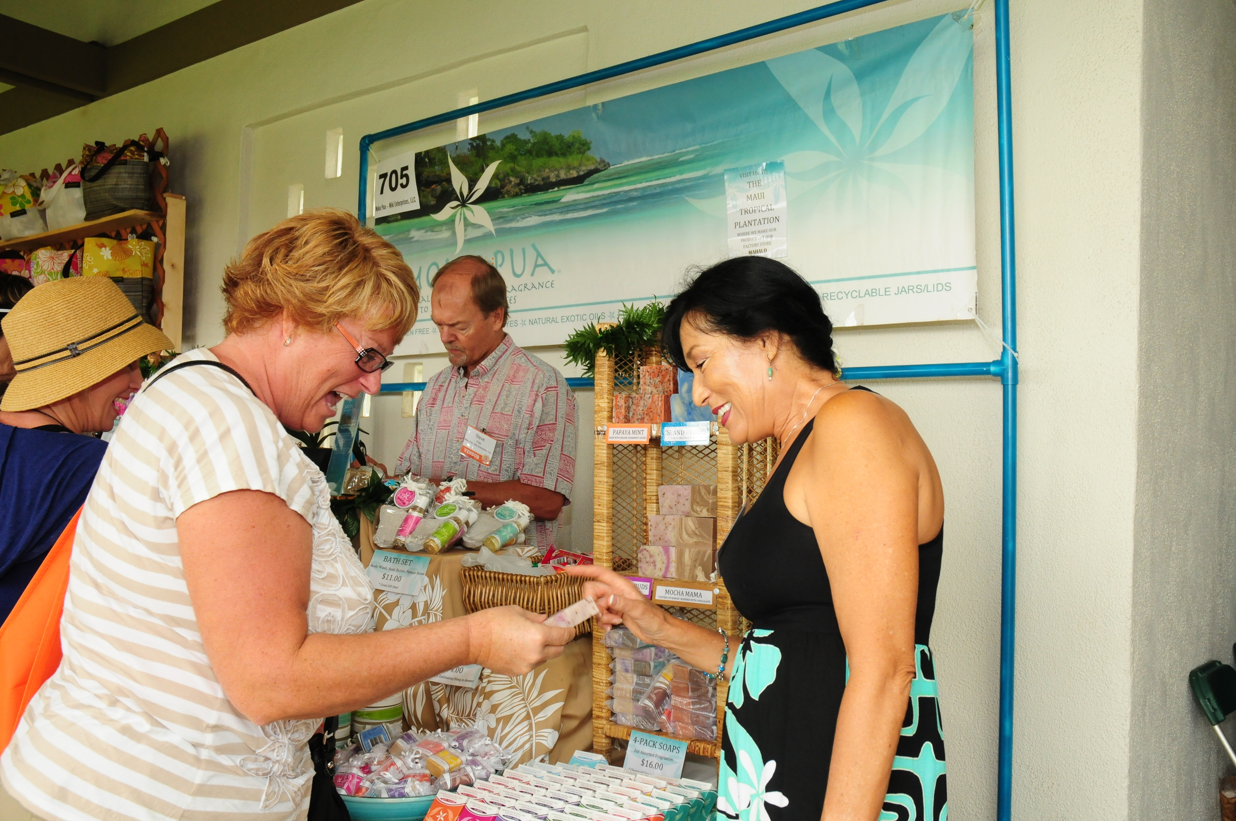 """Lori Hintzsche of Phoenix, Ariz., looks over a product made by Vicki Pillar of Moku Pua. Pillar said business was """"exploding,"""" and that she and her husband, Steve, picked up five new wholesale accounts and a steady stream of local customers and Maui visitors."""