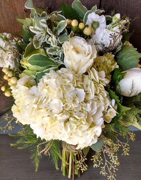 This view shows the focal point of the bouquet, a large white hydrangea surrounded by white and green roses, white stock and hypericum berries with snow on the mountain, tree fern and seeded eucalyptus for greens,