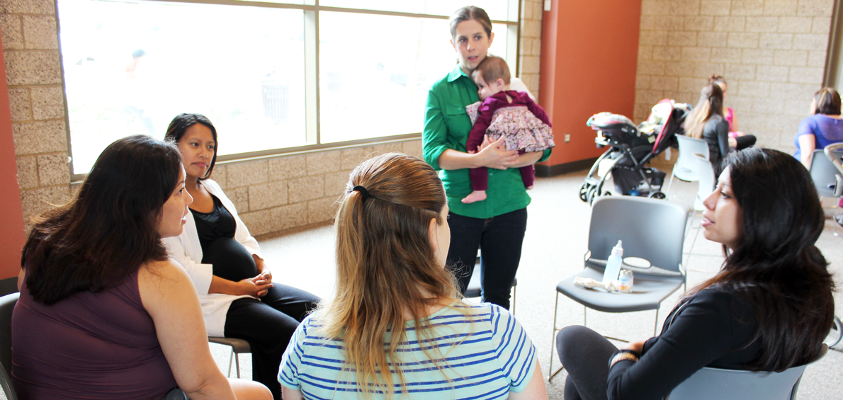 Moms-to-be sit in a small group with a Veteran Mom and her baby, asking questions about pregnancy, birth, breastfeeding, working, and more.