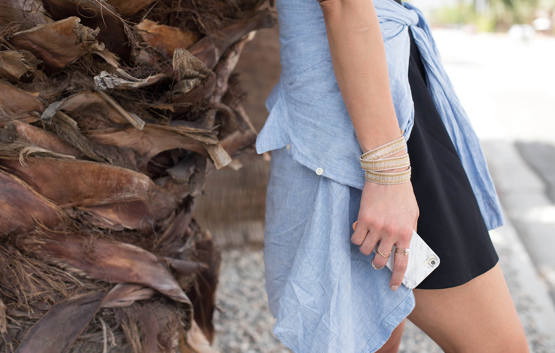 Side profile of outfit layering details with rings, bracelet and marble iPhone case.