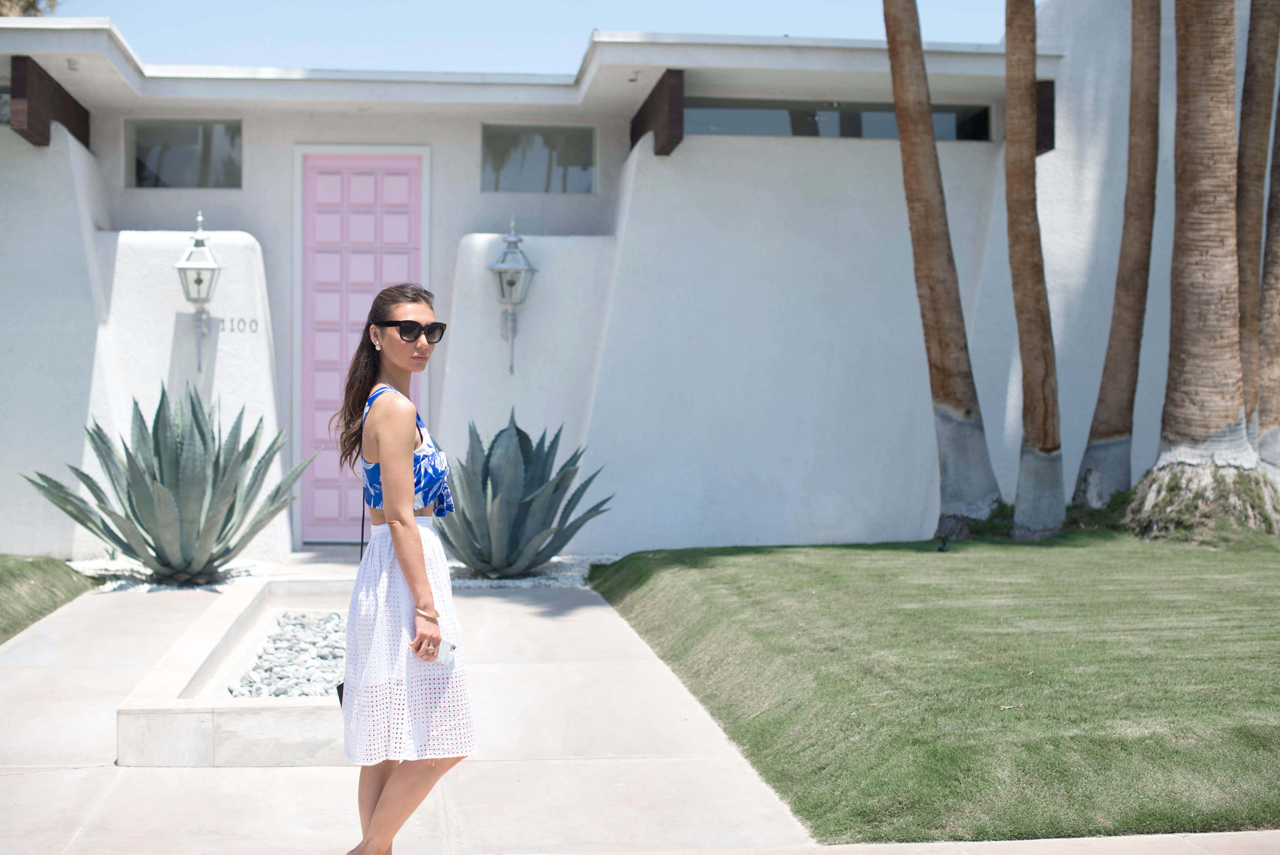 A girl in front of the pink door designed by Moises Esquenazi in Palm Springs