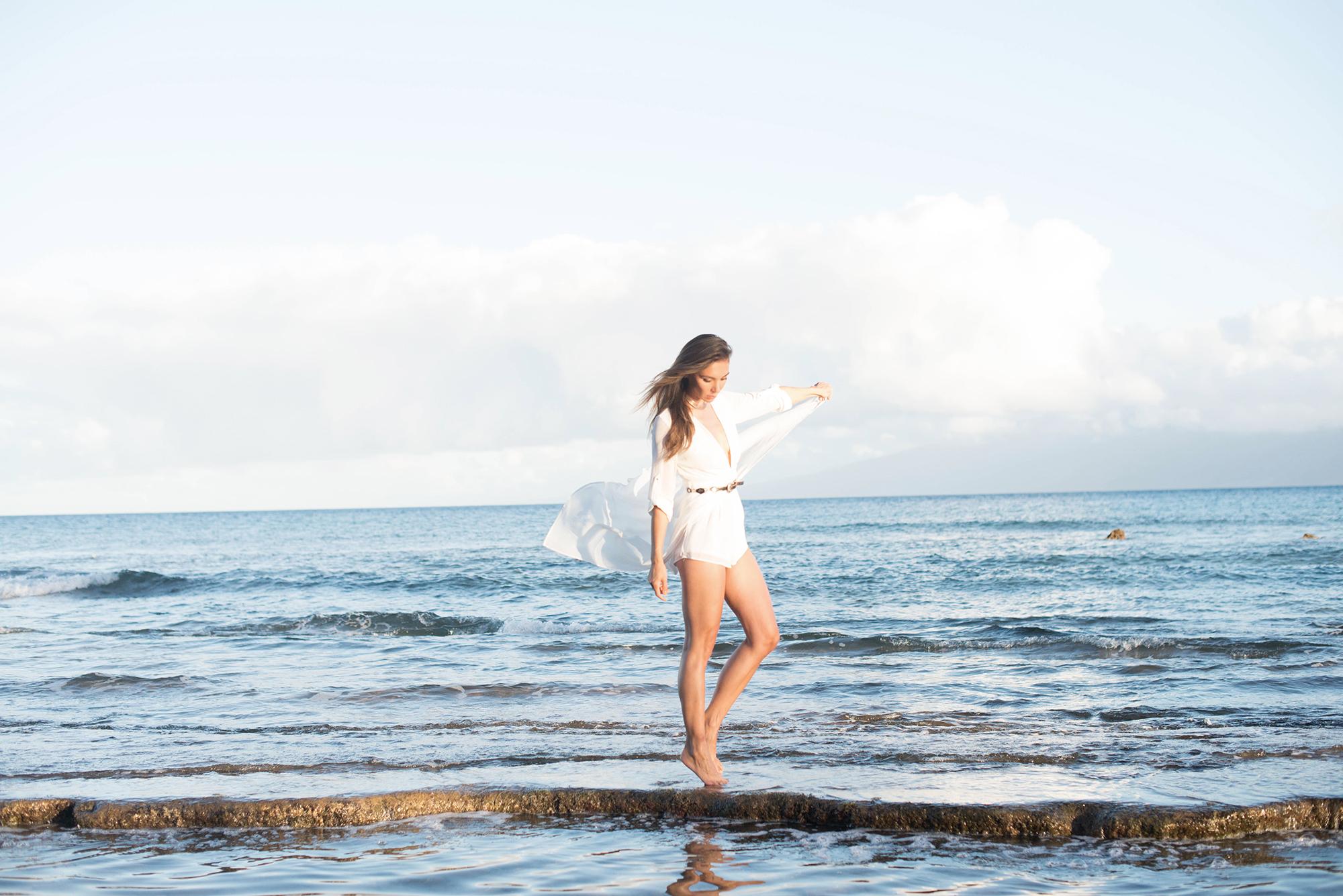 girl walking by the ocean in a white romper.