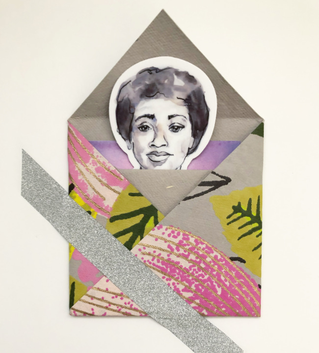 Sticker with Audre Lorde's portrait peaks out of a floral patterned origami envelope adhered to a white board with silver sparkle washi tape.