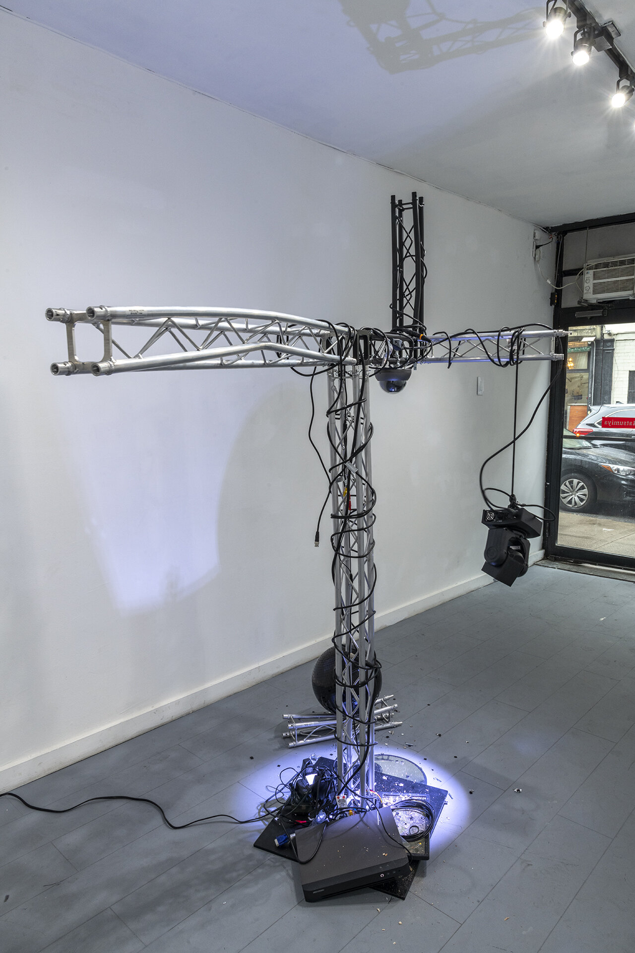 Craig Kalpakjian Damage Control, 2019  Lighting truss, surveillance mirror, security camera,  ADJ stage light, monitor, black mirrored ball, detritus 84 x 74 x 42 inches