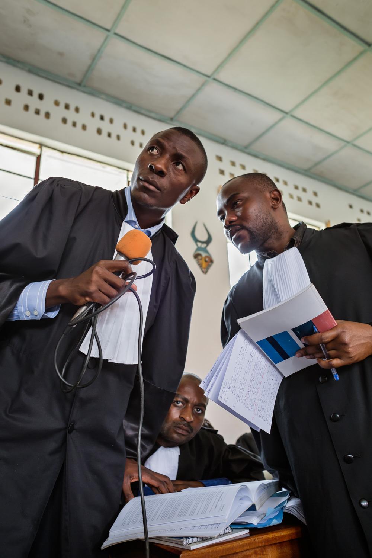 Three defense lawyers listen to a testimony and discuss their next response.