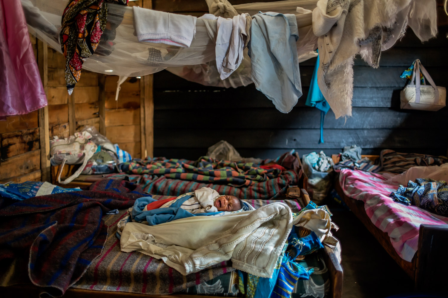 A two-week-old infant cries in a shelter for victims of sexual violence in the village of Buganga, two miles south of Minova. Founded by the activist Rebeca Masika Katsuva, a rape survivor herself, the center was home to more than 30 women and children during the attacks of November 2012.
