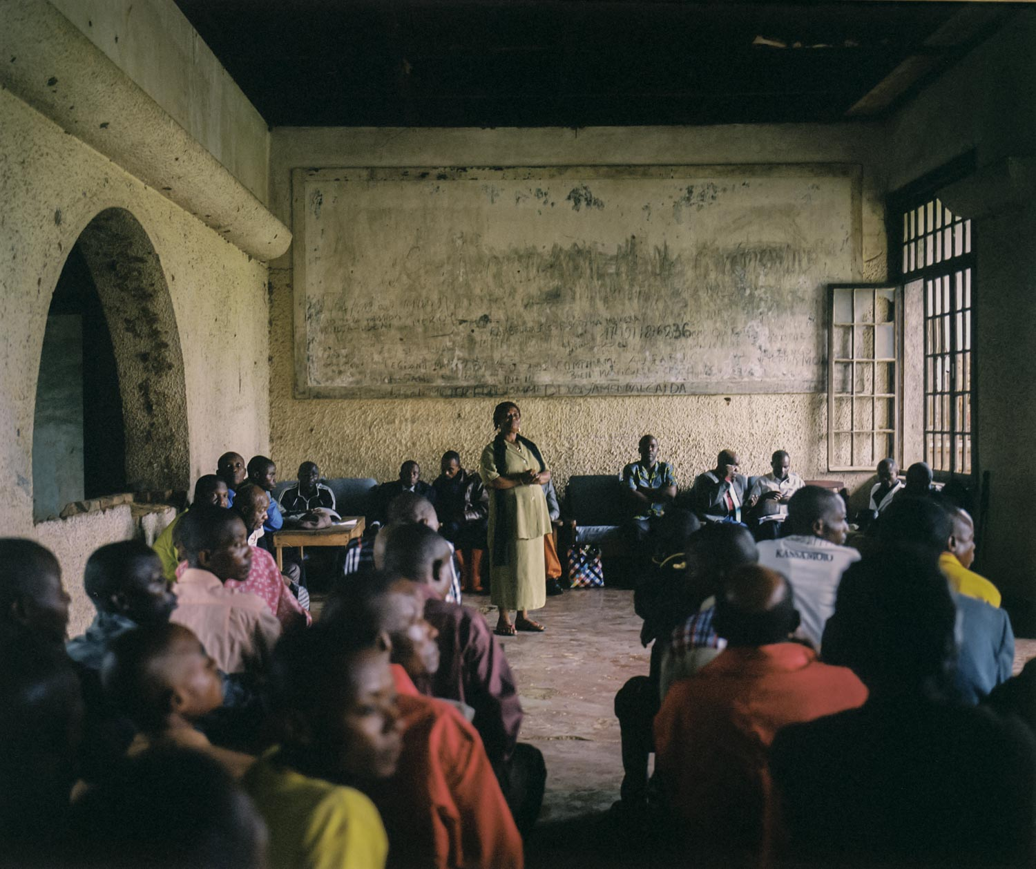 """Henriette Useni Kabake, Lulingu's government administrator, hosts a town meeting alongside traditional and Raia Mutomboki leaders inside a decayed building from the Belgian colonial era. The Raia Mutomboki insist they should not be labeled """"rebels"""" like other armed groups operating in Congo, citing that they have not interfered with the work of government officials in their territory.Dec. 28, 2013. Lulingu, South Kivu, Democratic Republic of the Congo."""