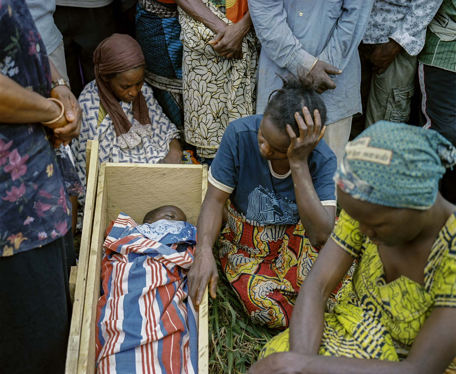 Villagers and family members mourn at the funeral of his murdered 7-year old son, Damas. The belief in sorcery includes a dogma that a rope used to commit suicide has inherent powers; the rope can be sold in markets in Burundi and Tanzania for thousands of dollars to believers that claim it will give them black magic powers. Damas' murder was staged to appears a suicide by hanging. Jan. 18, 2014. Lulingu, South Kivu, Democratic Republic of the Congo.