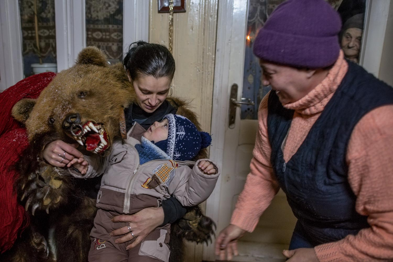 A lady bear in Toloaca's troupe plays with the young son of Cătălin Apetroaie, a bear dancer himself, after a performance at Apetroaie's home. The child's grandmother scurries by while his great-grandmother peers from inside the house.  December 28, 2014. Laloaia village, Bacău county, Romania.