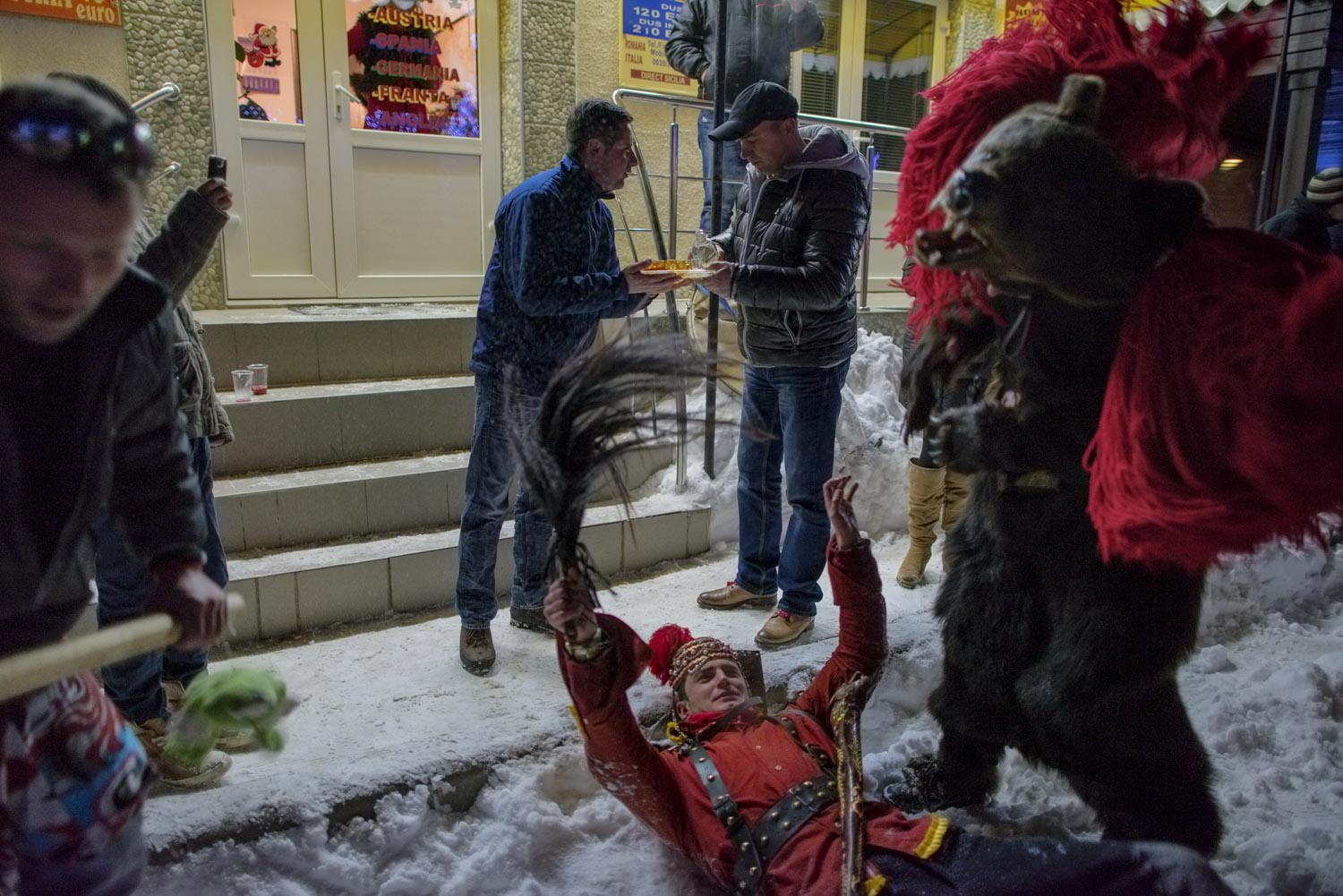 After winning first place at Comăneşti's annual Bear Parade, Toloacă's troupe celebrates in the streets, singing, dancing, and toasting with homemade palinka liquor handed out by the locals. December 30, 2014. Comăneşti town, Bacău county, Romania.