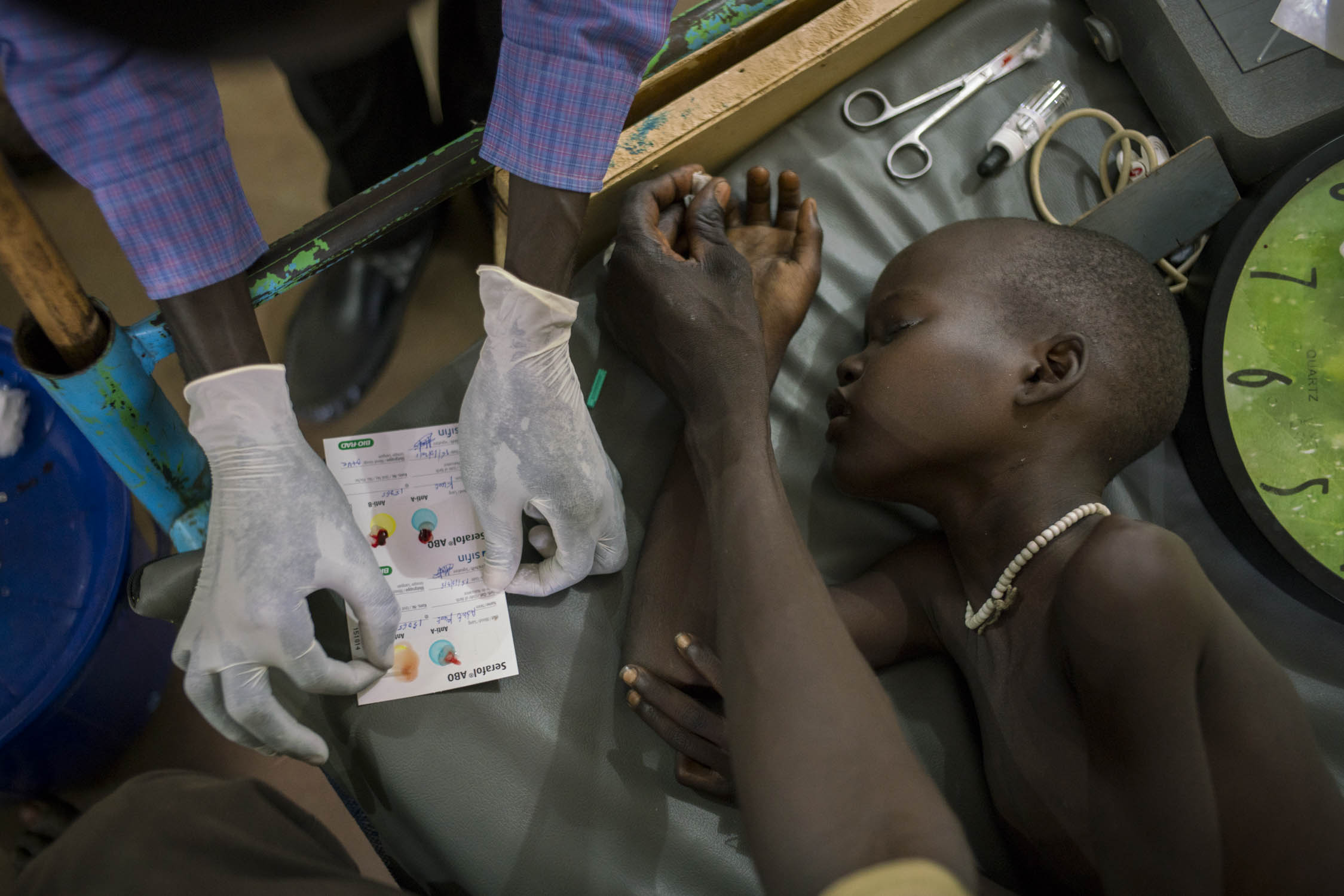 A nurse checks blood-type compatibility before administering a blood transfusion to Adut Chuor Kujal, 8, who is receiving treatment for cerebral malaria at an MSF hospital in Aweil city, South Sudan. Adut's father presses down on her fingertip that has just been pricked to obtain a blood sample. Adut's family lives in a remote rural village so she had been sick for several days before her father made the journey to Aweil. He had first taken her to a private clinic closer to their home but they had no malaria drugs in stock. South Sudan is host to one of the deadliest conflicts in the world, yet in 2015, malaria killed more people than bullets. Across the country, 2.28 million cases of malaria were reported. Aweil, Northern Bahr el Ghazar state, South Sudan. October 15, 2015
