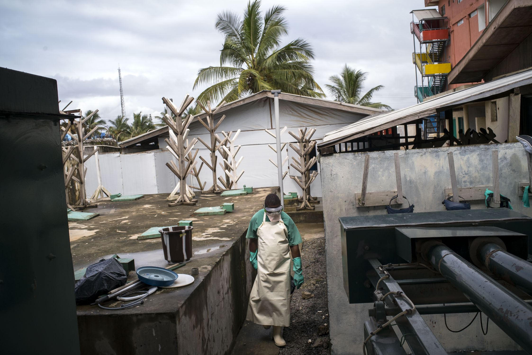 A sanitation worker walks though the back courtyard of an MSF hospital in Monrovia, Liberia. In the aftermath of the the ebola epidemic of 2014/15 that left an estimated 4800 dead in Liberia, the hospital adheres to especially strict routine sanitation measures. Monrovia, Liberia. Sept. 28, 2016