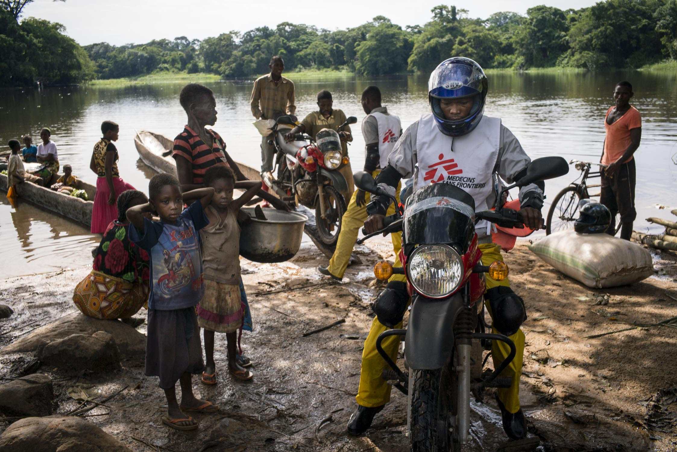 MSF drivers disembark their motorcycles from the local  pirogues  (traditional canoes) used to cross a river on their journey to a health center in Sombe, a village in the remote Bas-Uele province of Democratic Republic of the Congo (DRC). MSF arrived to the area to carry out a five-day measles vaccination campaign in response to a measles epidemic. MSF had named measles among the top five epidemics that could erupt or worsen in 2016. DRC has the fifth highest under-five mortality rate in the world. An estimated 465,000 children in DRC die each year of preventable diseases. Bas-Uele province, Democratic Republic of the Congo. May 28, 2016