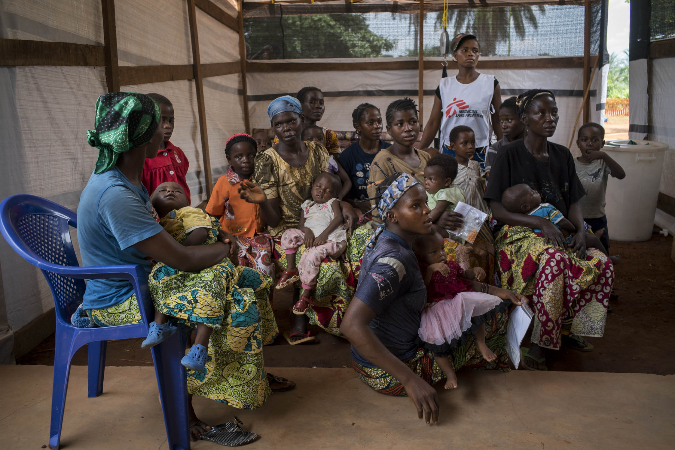 Mothers hold their sick children in the crowded waiting room of the MSF wing at a hospital in Monga, a town in a remote northern region of Democratic Republic of the Congo. MSF arrived to the area in response to a measles epidemic, therefore, only children with a fever were referred to the MSF wing. Monga, Bas-Uele province, Democratic Republic of the Congo. May 26, 2016
