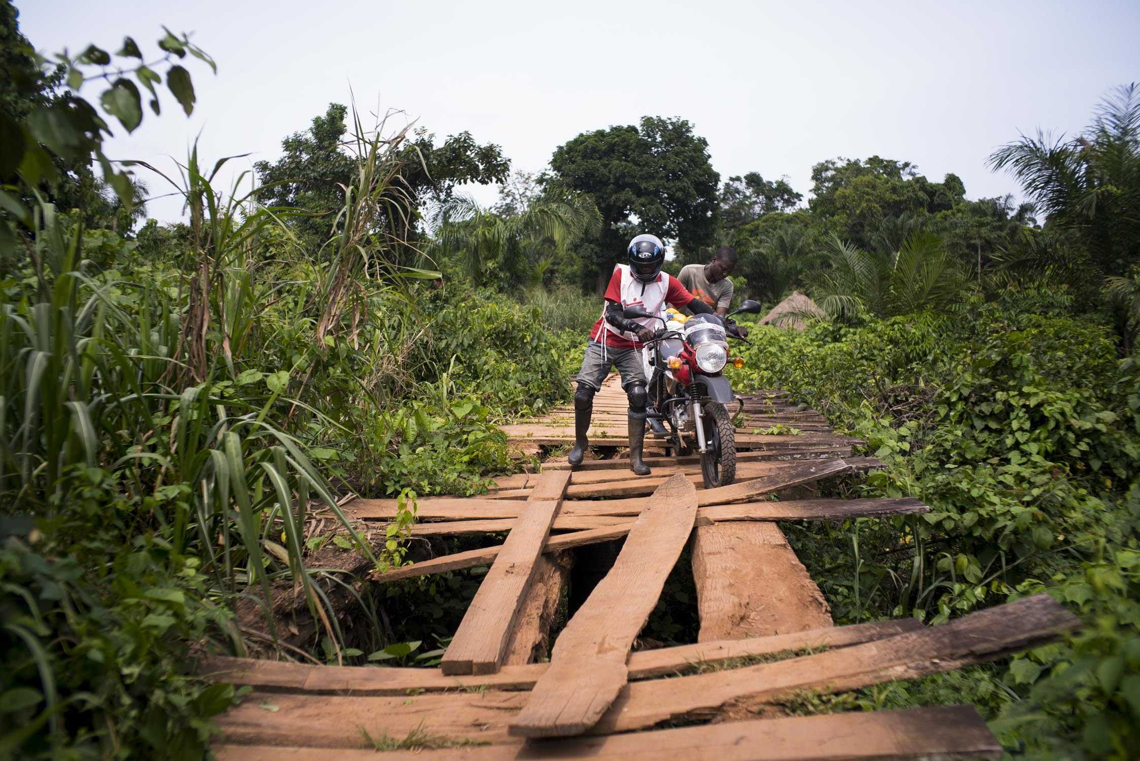 A MSF driver struggles to push his motorbike over a bridge on the route to the health center in the village of Nzeret, the epicenter of a measles epidemic that spread through this remote northern area of Democratic Republic of the Congo (DRC) in early 2016. The bridge had been in even worse shape until MSF purchased additional wooden planks and hired a crew of local workers to fortify it earlier that day, a necessary measure in order to carry out their planned 5-day measles vaccination campaign. MSF had named measles among the top five epidemics that could erupt or worsen in 2016. DRC has the fifth highest under-five mortality rate in the world. An estimated 465,000 children in DRC die each year of preventable diseases. Nzeret, Bas-Uele province, Democratic Republic of the Congo. May 27, 2016