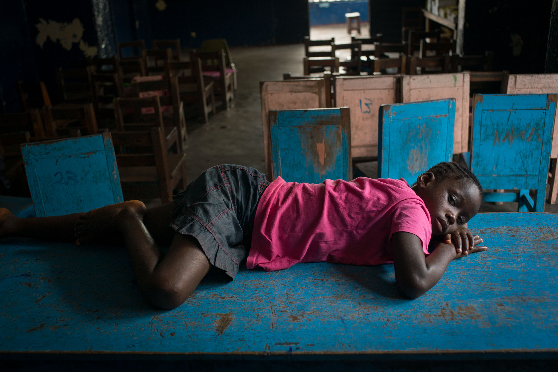 A youg girl suffering from malaria lies on a table after the classroom empties out at a Bridge school. One of the challenges to education in the developing world is that children come to school sick, so good schools usually supply medical referrals or care. September 23, 2016. Monrovia, Liberia.