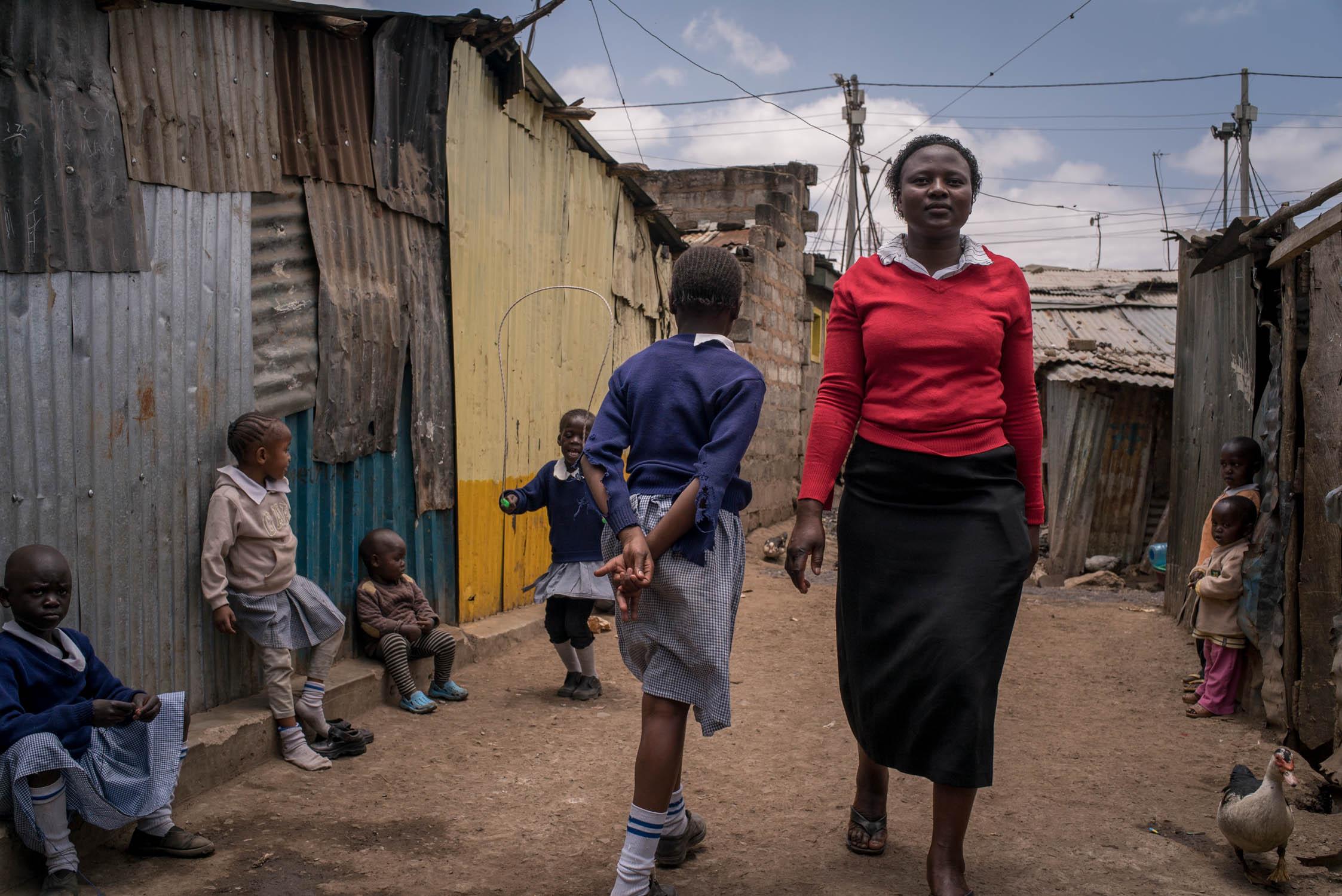 A teacher walks past children at a school (not Bridge) in Mathare slum area of Nairobi. September 19, 2016. Mathare slum, Nairobi, Kenya.