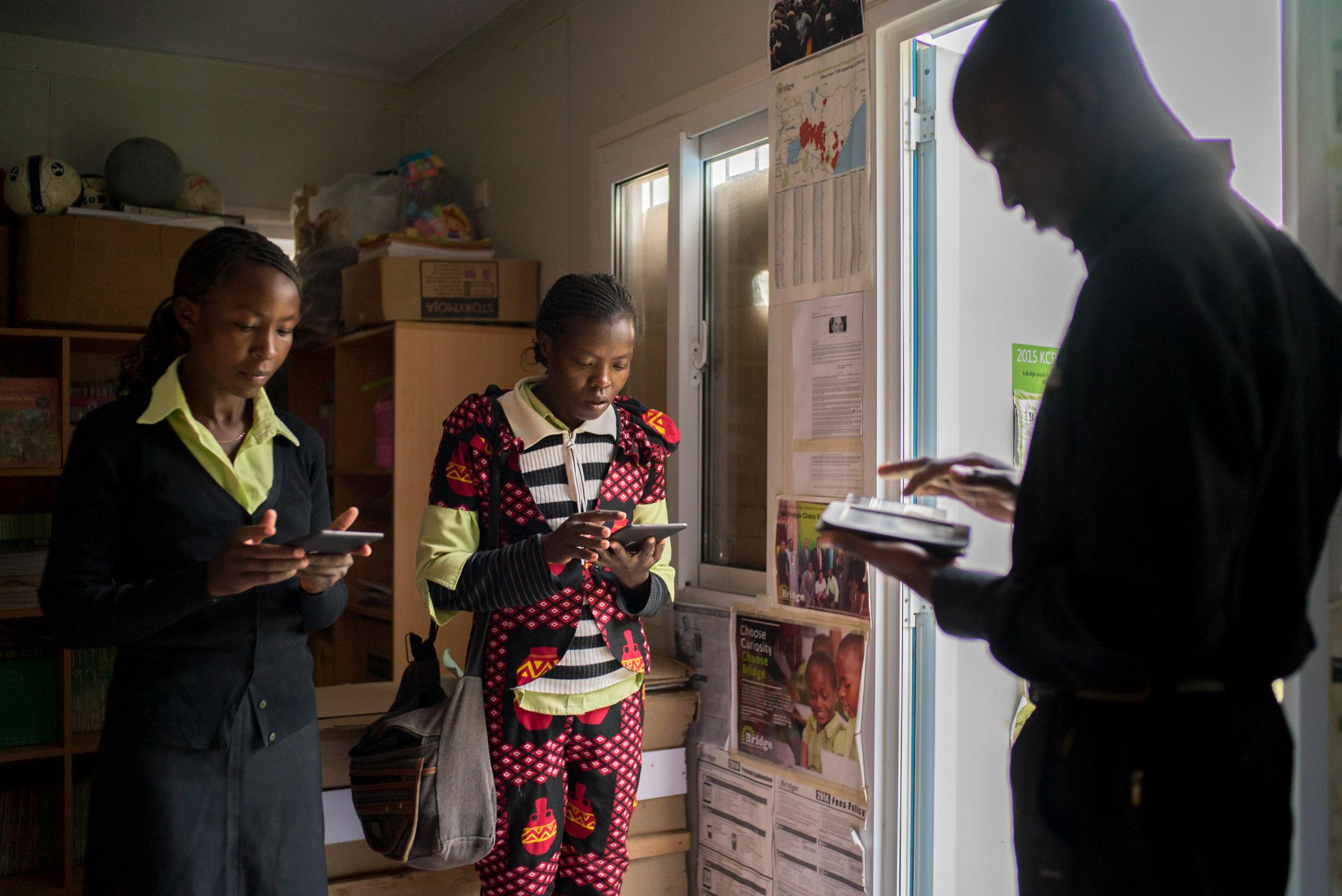 At the start of the schoolday, teachers receive their lesson plans for the day on their Nooks, at Kiserian Bridge school in Nairobi. September 20, 2016. Kiserian, Nairobi, Kenya.