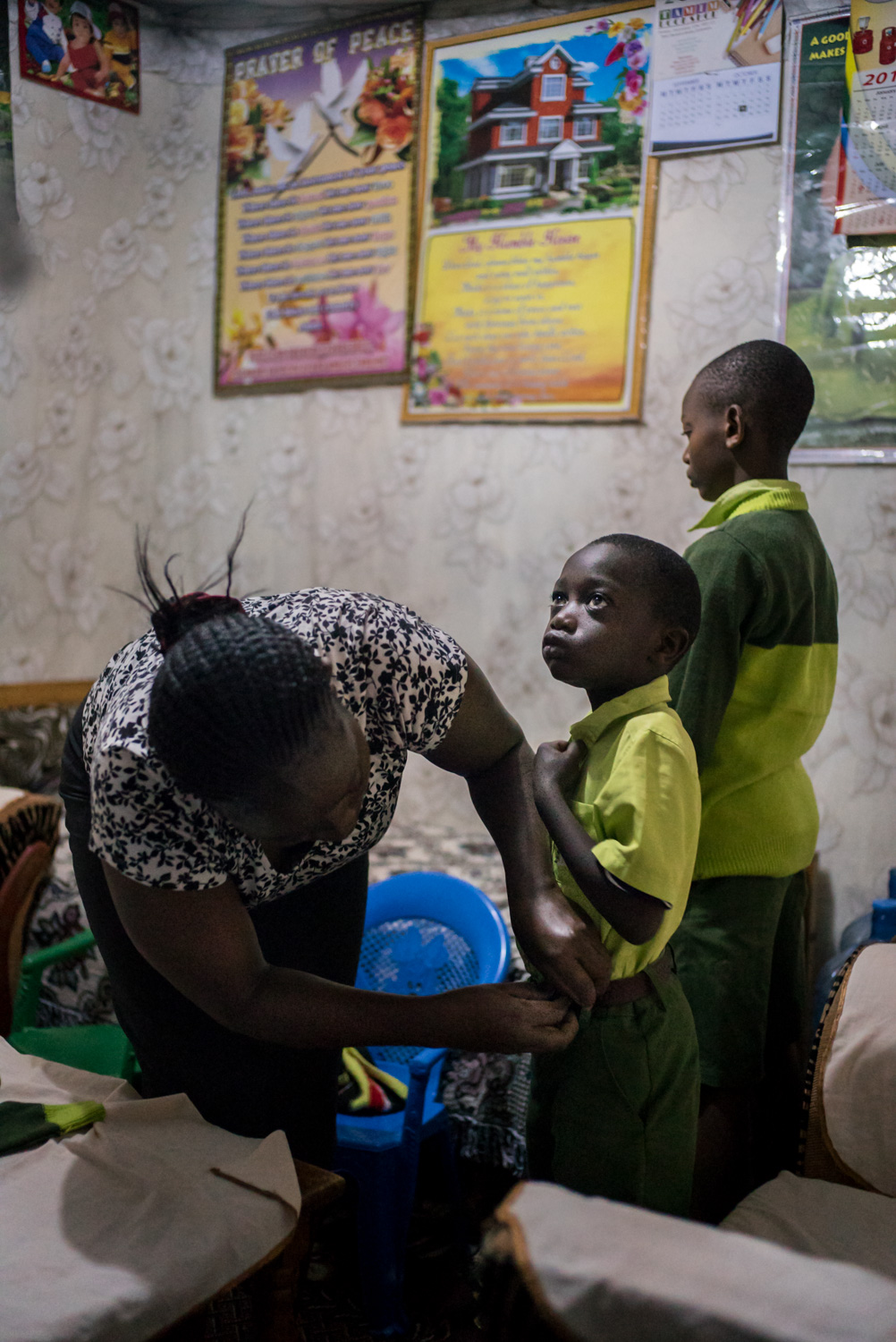 Elizabeth Mumo prepares her sons Samuel, 6, and Joshua, 12, for another schoolday at Bridge. She and her husband save to pay school fees for her two sons to attend Bridge, believing that since the school is run by white westerners, her children are getting the same kind of education as the children of expats and diplomats-- an international education that she hopes may one day land her children at Oxford University. September 20, 2016. Nairobi, Kenya.