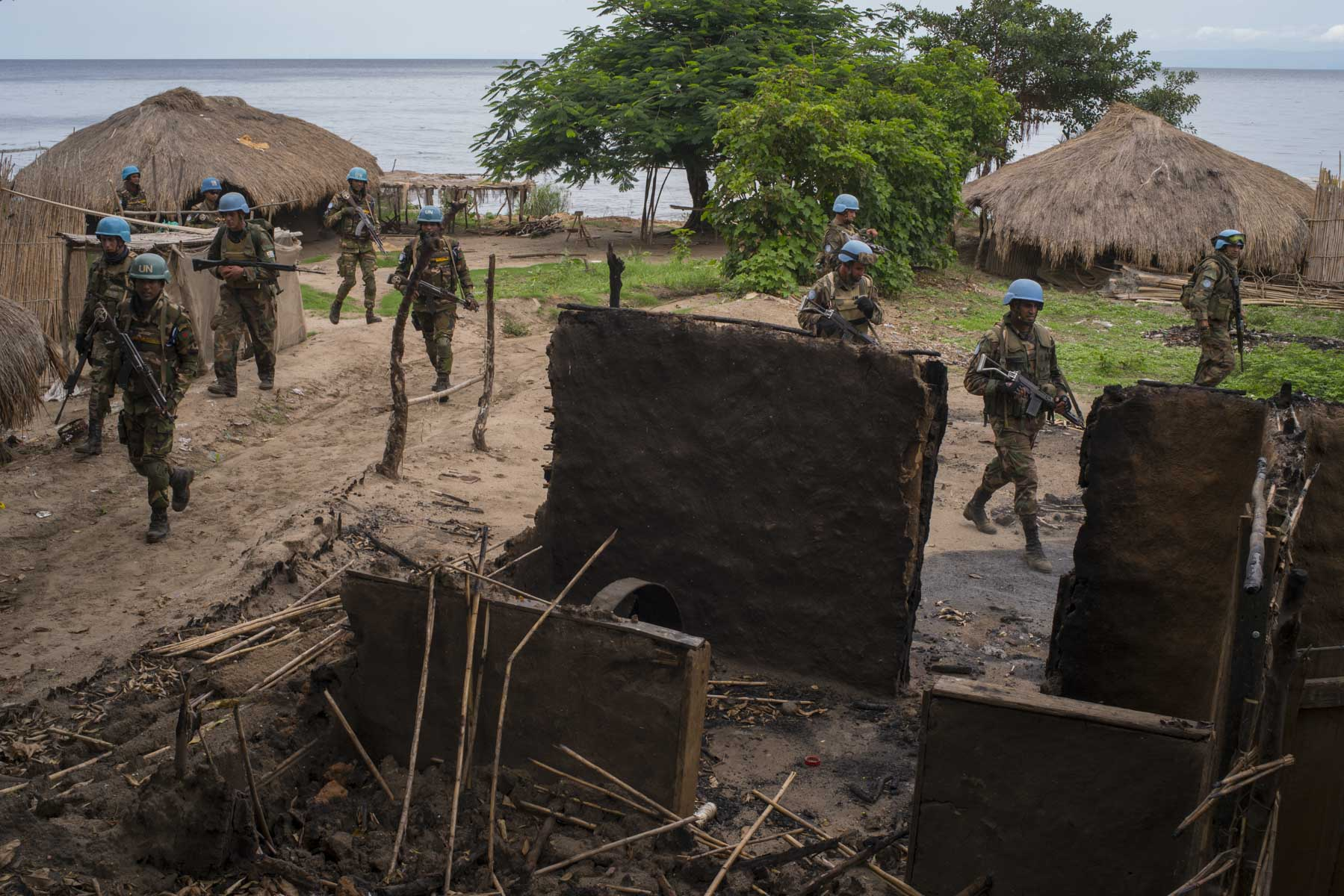 Soldiers from the Armed Forces of the DRC, and UN peacekeeprs from the Uruguyan and Bangladesh batallions move through Ghat, a deserted lakeside village that lies in ruins after attacks from militias less than a week prior. They have come here to meet six Uruguyan soldiers who after succeeding to reach Joo, a decimated village further up the coast, were stuck there for three days and nights, surrounded by militias. March 18, 2018. Ghat, Djugu territory, Ituri province, Democratic Republic of the Congo. Diana Zeyneb Alhindawi for The New York Times
