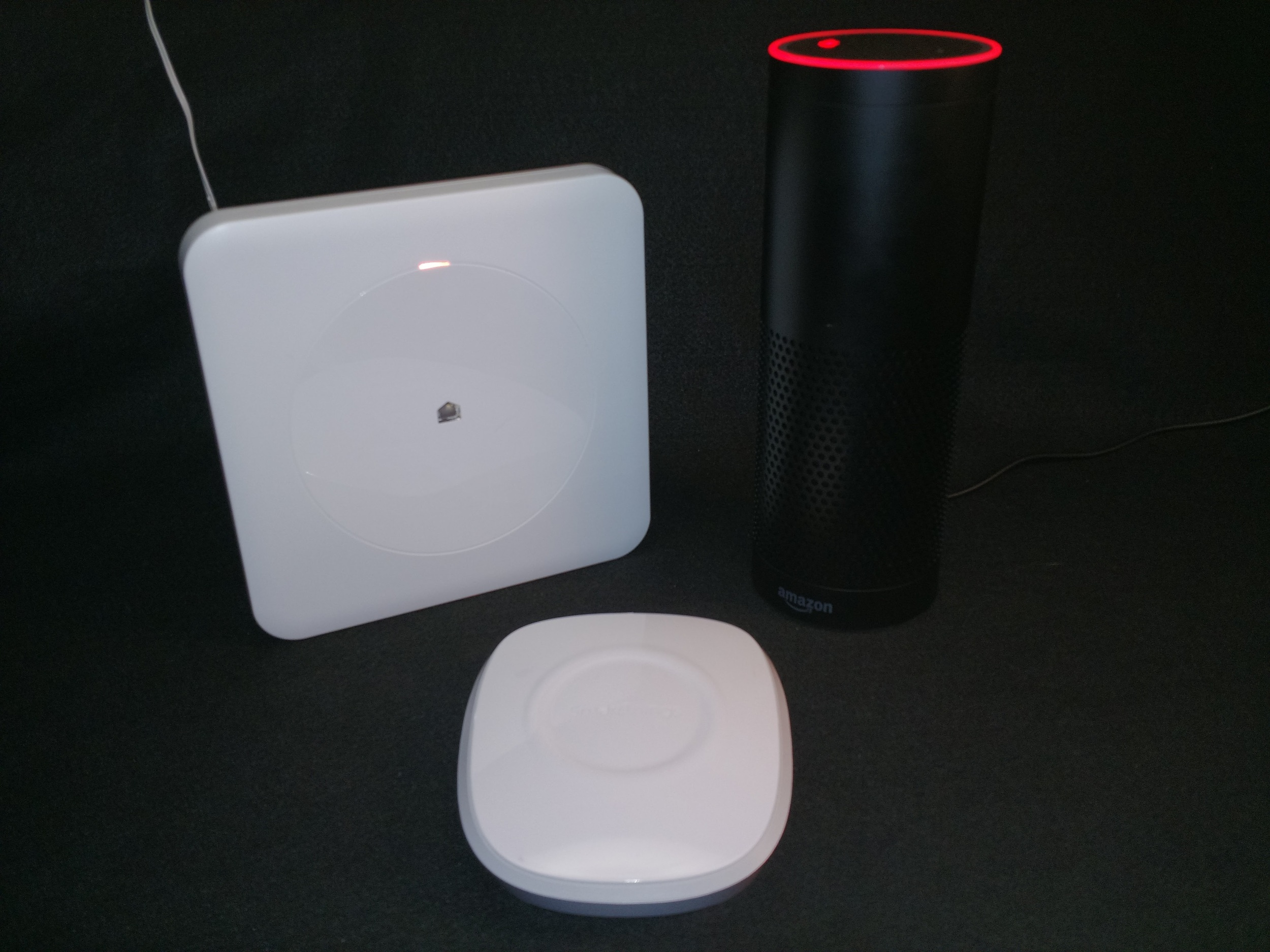 From left to right: The Wink Hub, The SmartThings Hub, Amazon Echo (muted to show the red ring)