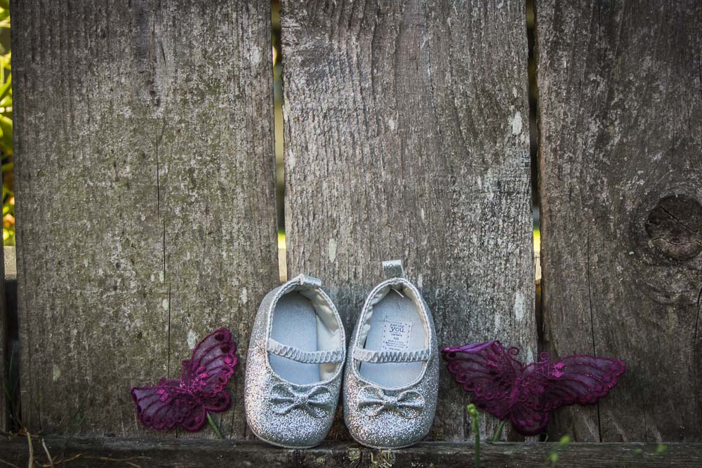 Sparkly Baby Shoes On Rustic Fence by Captured By Katie Photography, Tacoma Maternity Photographer
