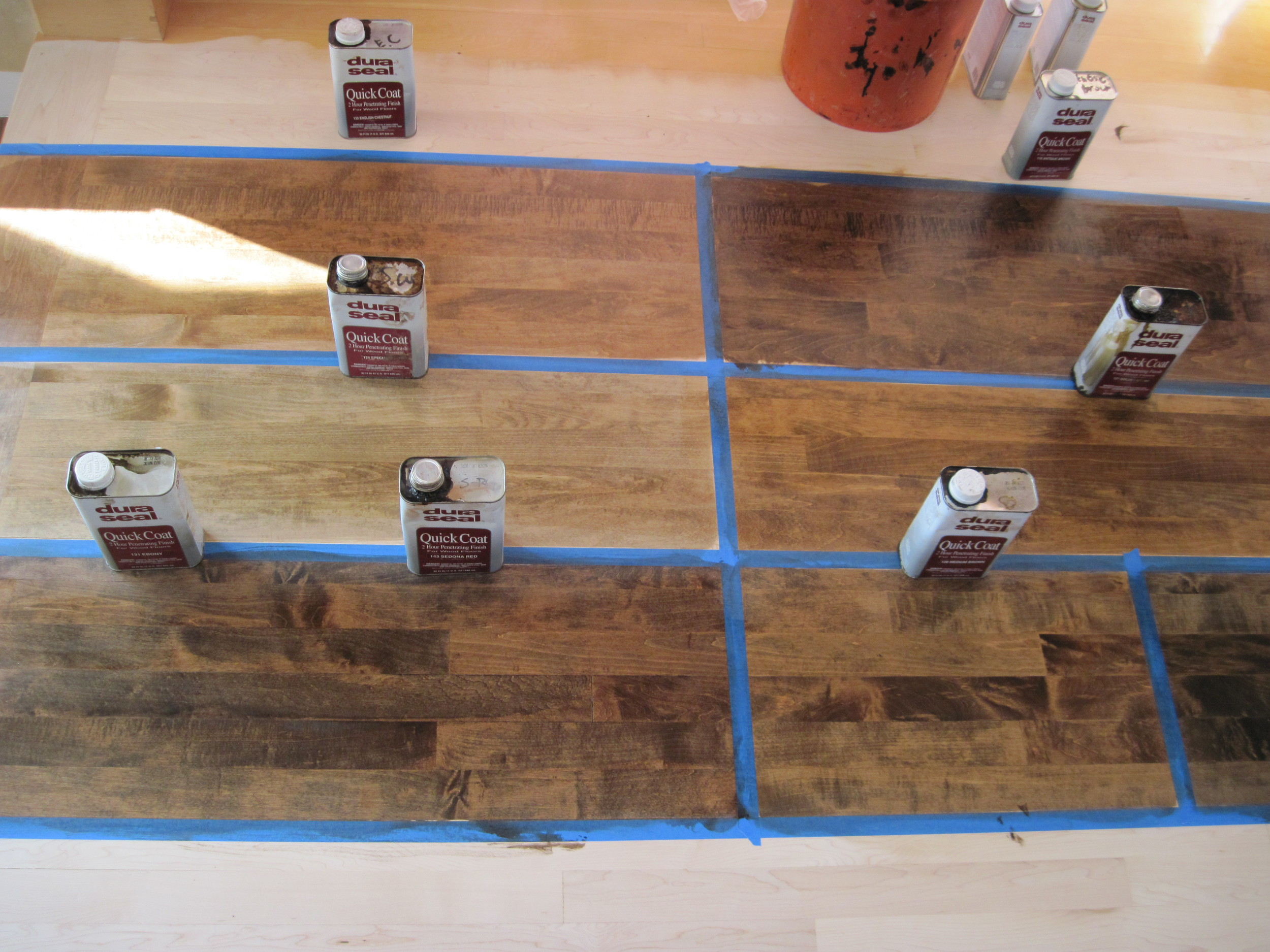 During the sanding phase, different stains can be applied to your floor, so you can choose which you like best. Pictured here: sample stains on maple flooring.