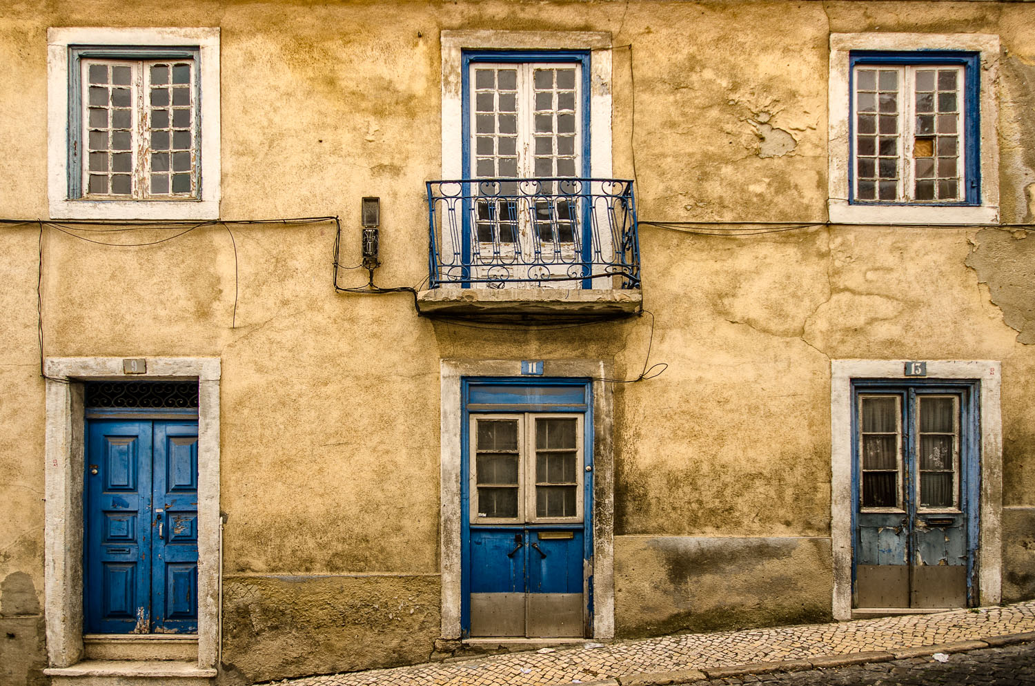 A yellow/golden wall with blue framed windows and blue doors - photo taken in Bairro Alto during a Lisbon photo tour...