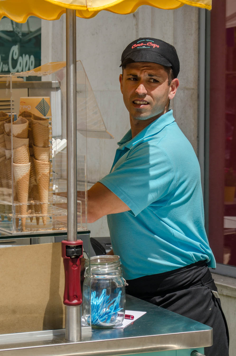 Last summer during a photo tour in Lisbon, I came across this young man selling ice-cream. Including part of the environment adds the bright colours and helps telling the story. Had I gotten too close and all I would get would be the photo of a young man in a funny hat.