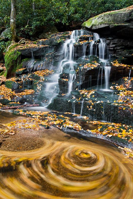 """Elakala Whirlpool"" - A long exposure shows a striking swirl of autumn leaves below a waterfall. Elakala Run, Blackwater Falls State Park, West Virginia."