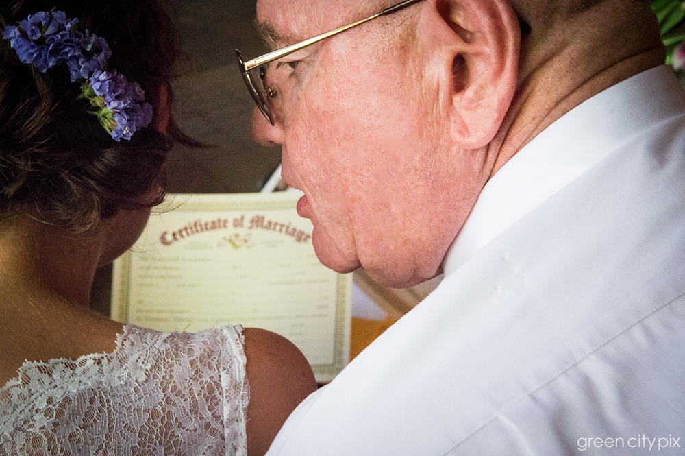 The officiant explains the details of signing the Certificate of Marriage.