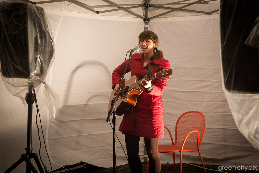 Singer  Lydia Ramsey  belting out a tune. Her songs convey the wildness of the Northwest and are steeped in the fingerpick-guitar rudiments of folk music.