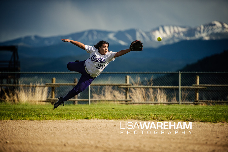 Sports photos during senior portraits can add impact to your portraits. Tristan above jumps for the ball with a background of the Montana mountains.