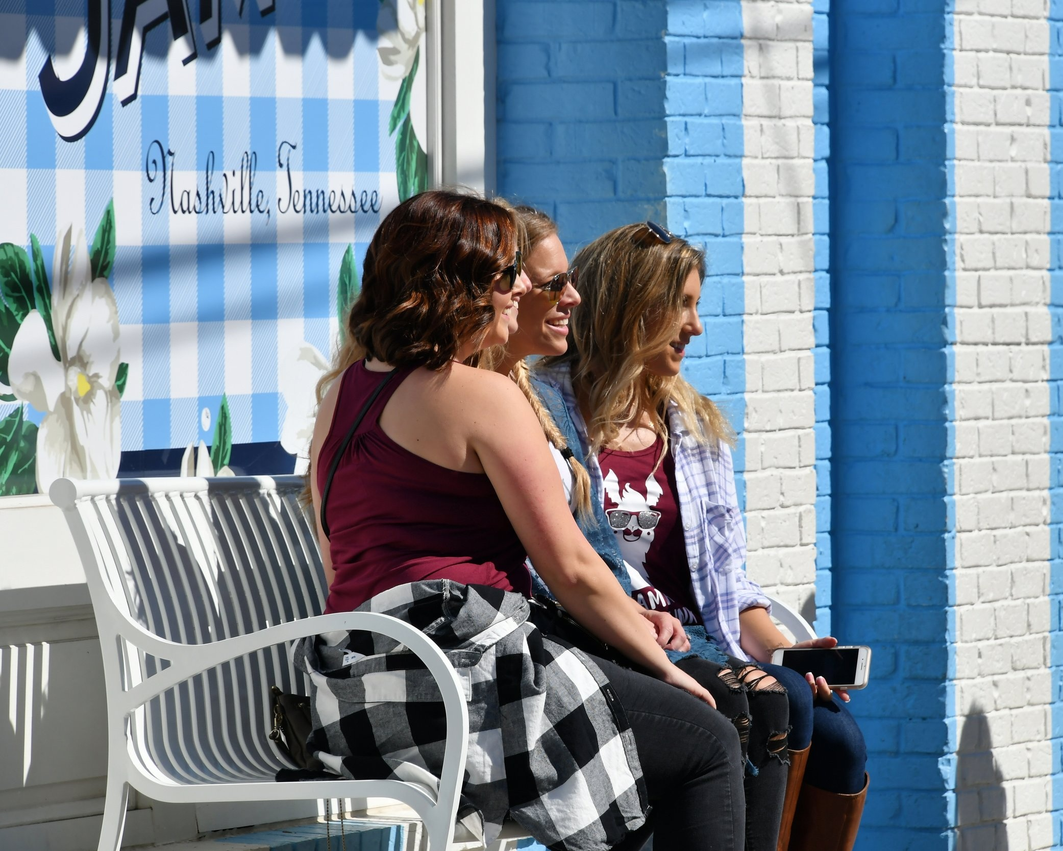female-tourists-and-friends-pose-to-get-their-photos-taken-in-front-of-the-blue-and-white-striped_t20_Ywmgdm.jpg