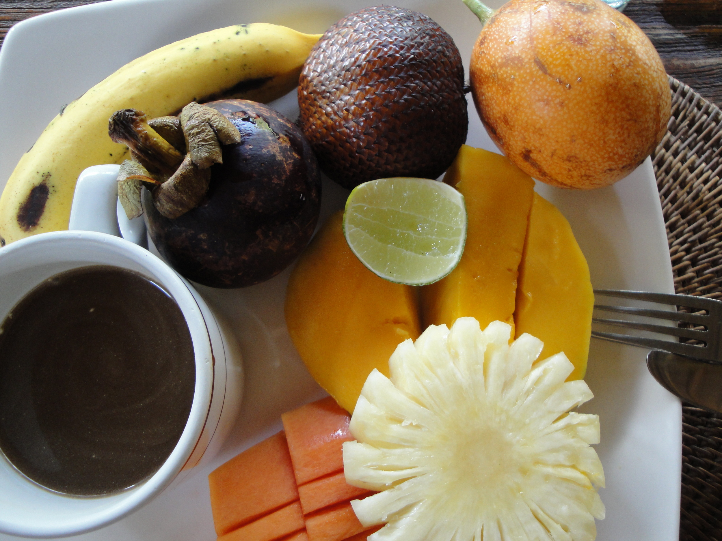 Tropical local fruit and Bali coffee with coconut milk for breakfast.