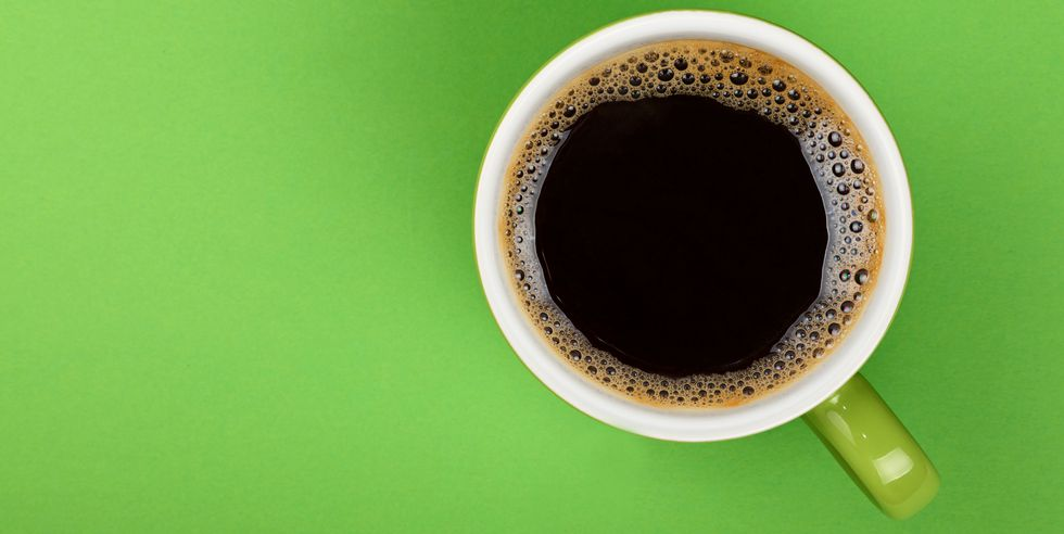 directly-above-shot-of-black-coffee-in-cup-on-green-royalty-free-image-931632020-1560374164.jpg