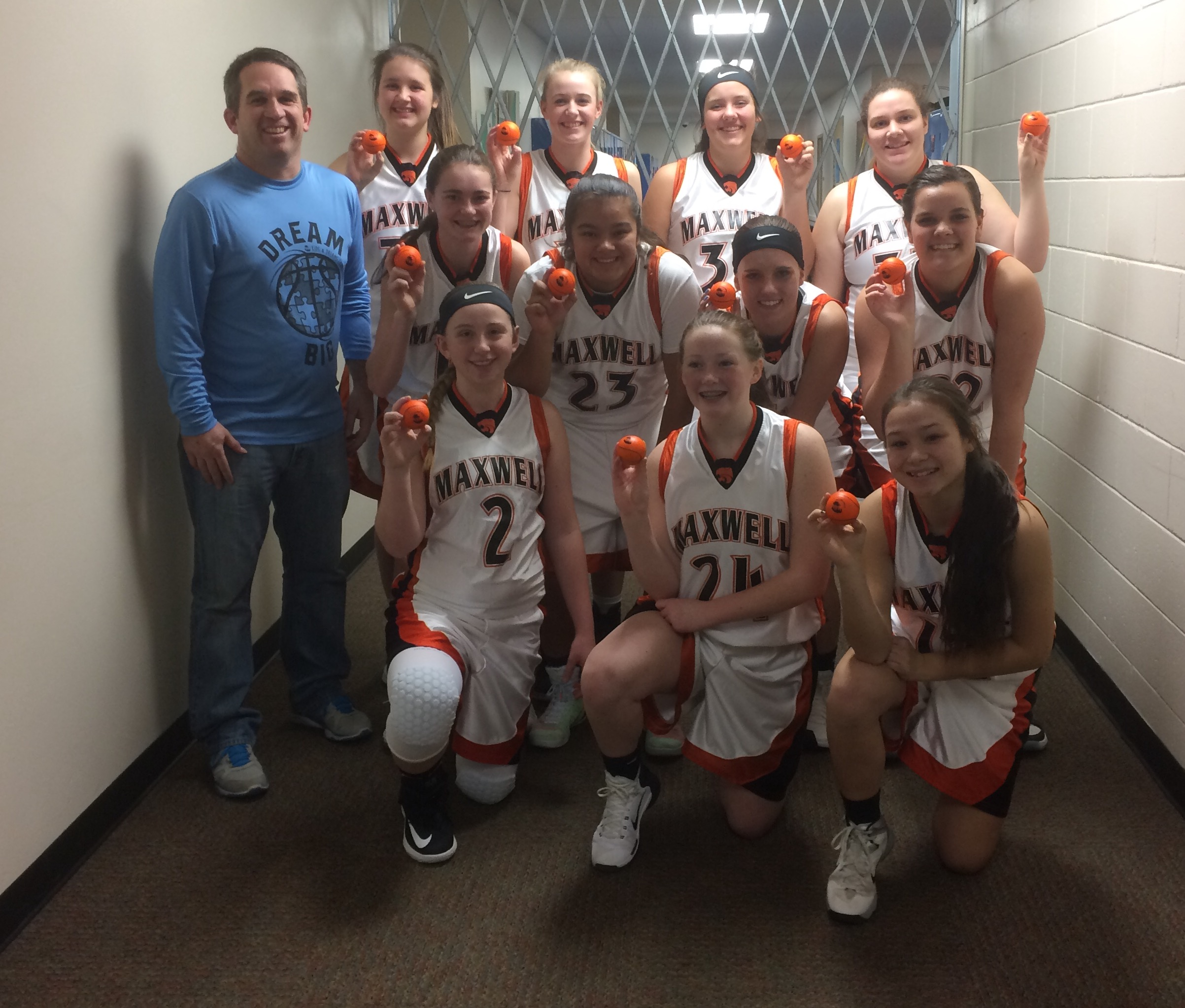 """The Maxwell Tigers girl's basketball team helping us out by throwing out autographed """"Kids & Dreams"""" stress basketballs."""