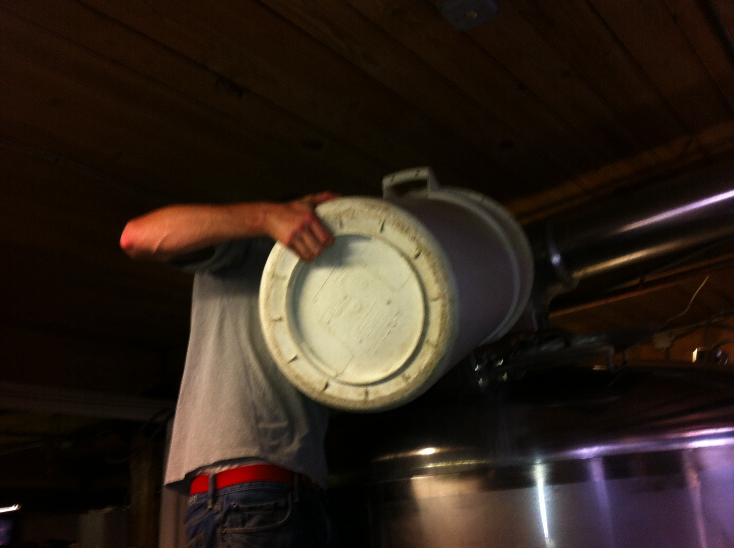 Pouring peaches into the kettle to mix with the wort and sterilize