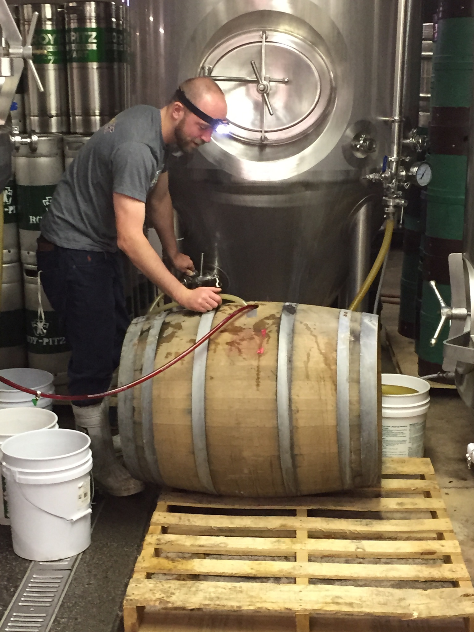 Chris Collier filling a white wine barrel with Mind Your P's and Q's