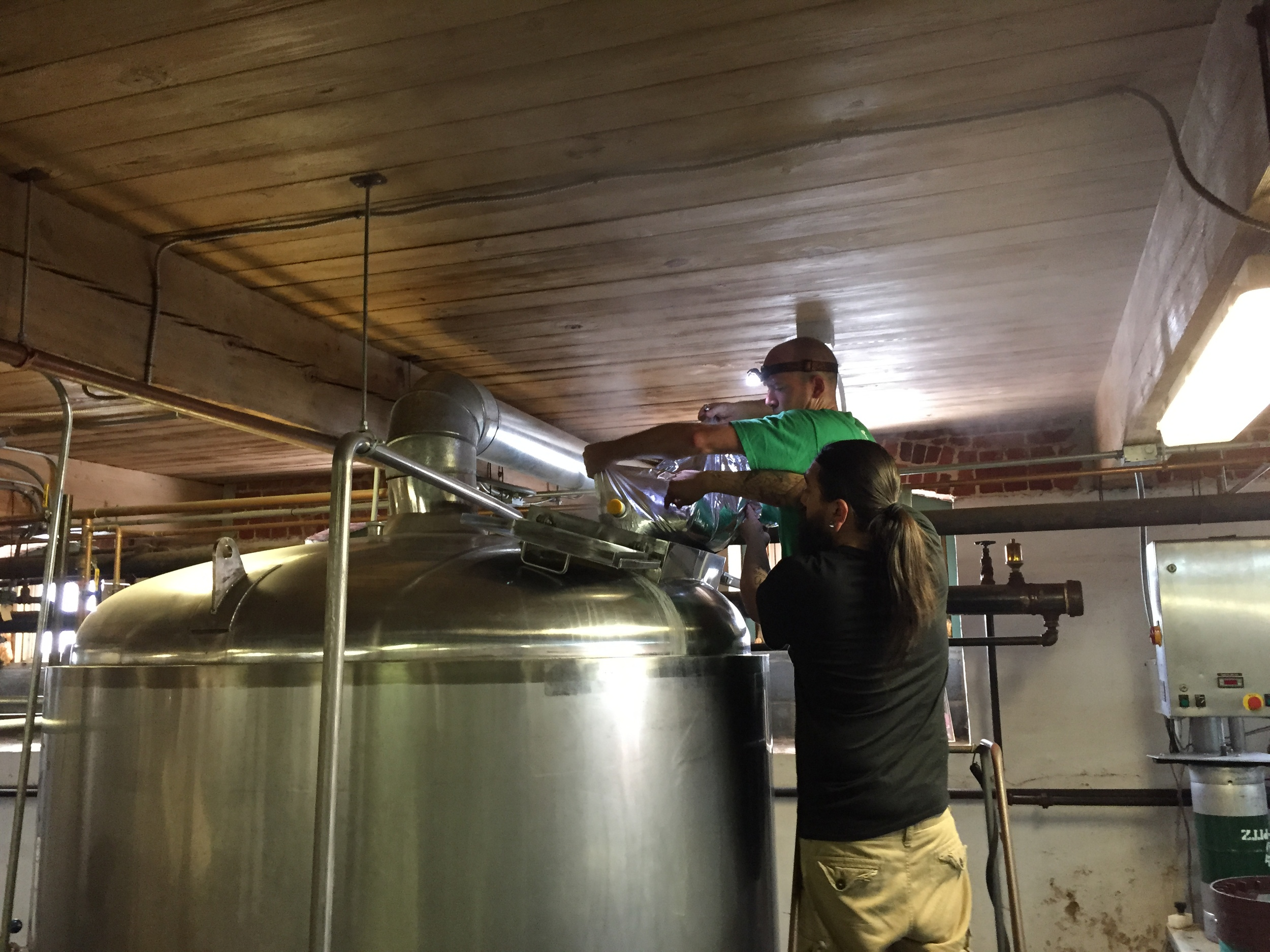 Chris and Berto adding blueberry to the kettle for the Schnozberry Lager