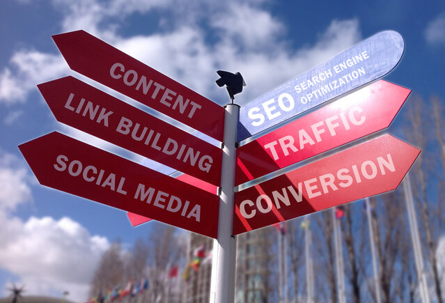 Street signs showing SEO, content, link building, social media, traffic, and conversion