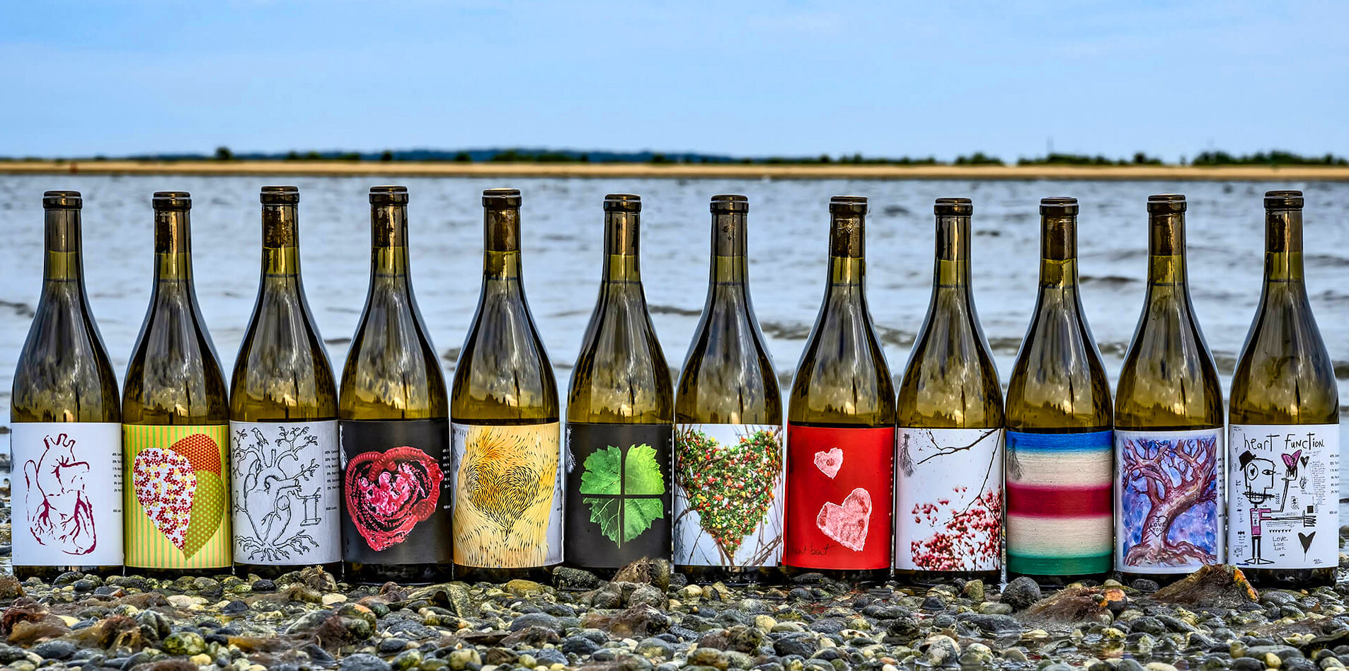 2019 Heart Artists Series wine bottles lined up on the beach