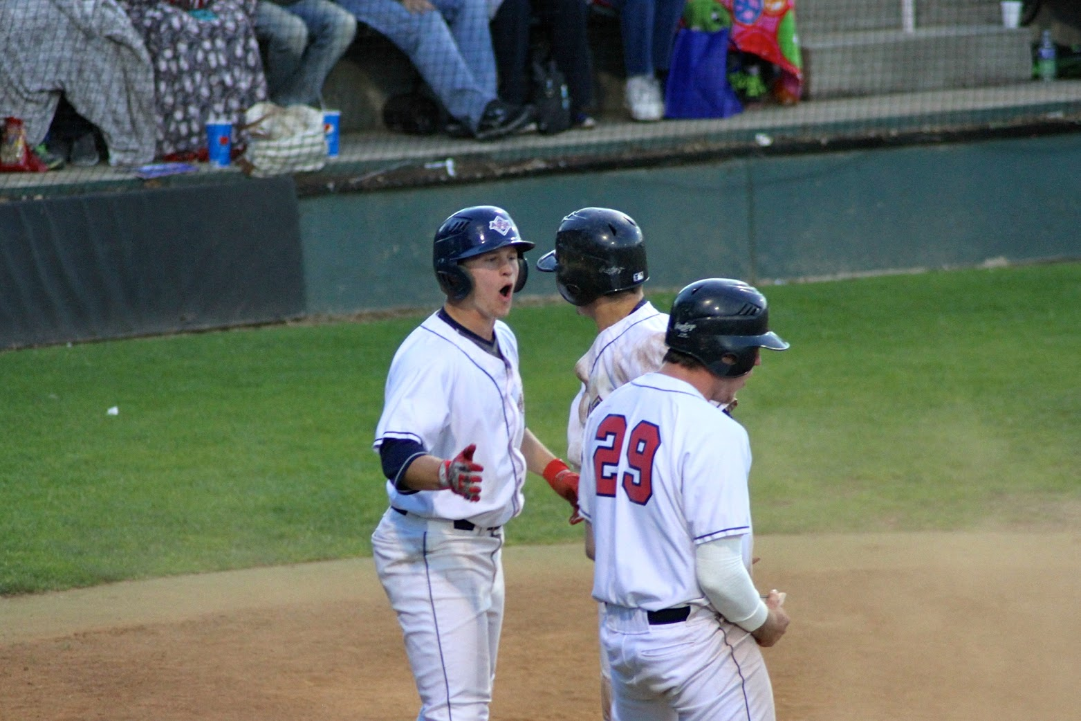 Jordan Rathbone, Steven Machtolf, and Ryan Murkle celebrate after being driven in on a bases-clearing double for Haydan Hastings in the sixth inning of a 6-3, AppleSox win, Saturday.