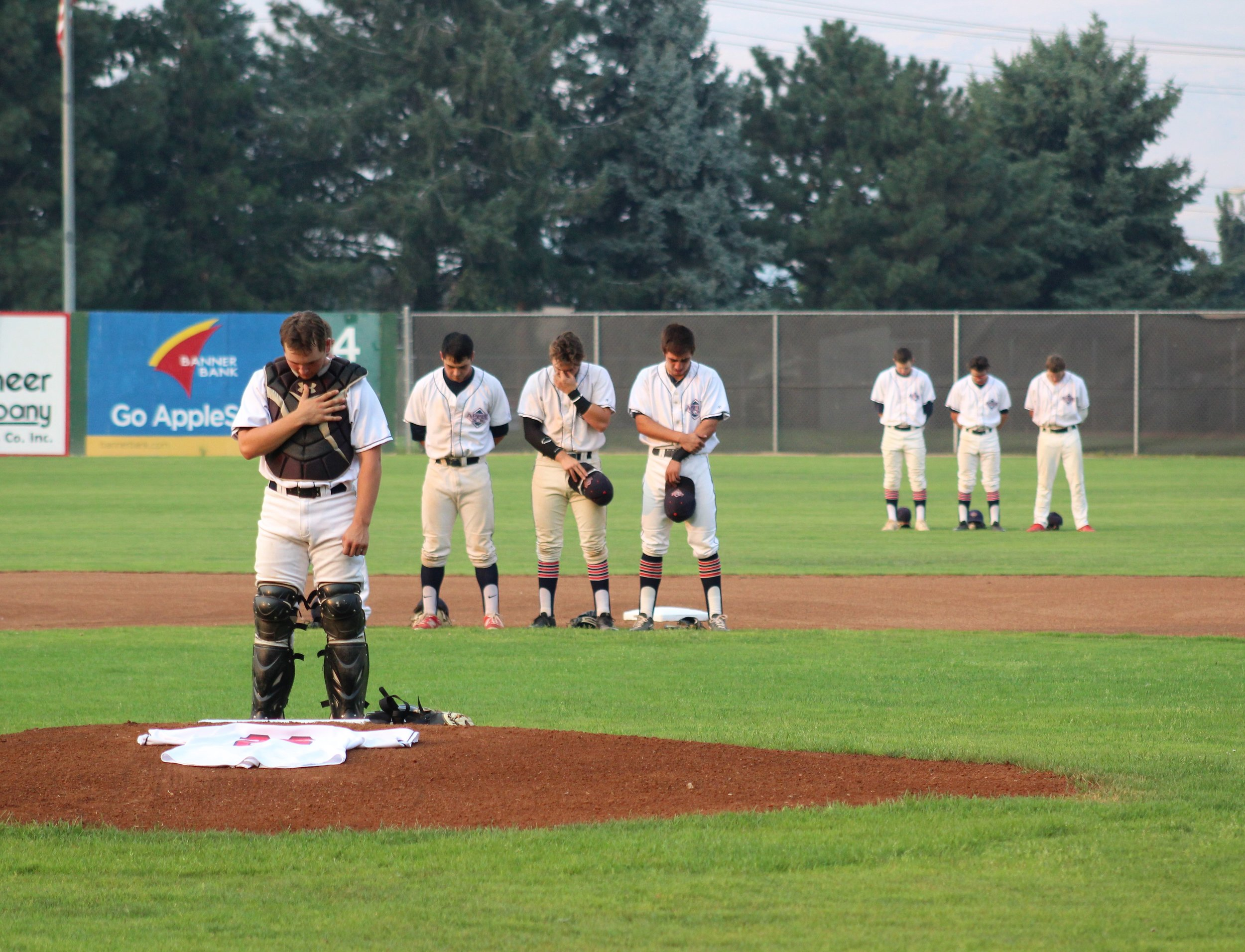 AppleSox players take pause for a moment of silence, Monday night. Wenatchee honored teammate Tommy Watanabe who passed away unexpectedly, Saturday, after playing with the AppleSox through July 22. Watanabe was the team's starting pitcher in the final game of 2017, and they brought his jersey to the mound for the moment of silence and National Anthem. Photo by Alyssa Taylor.