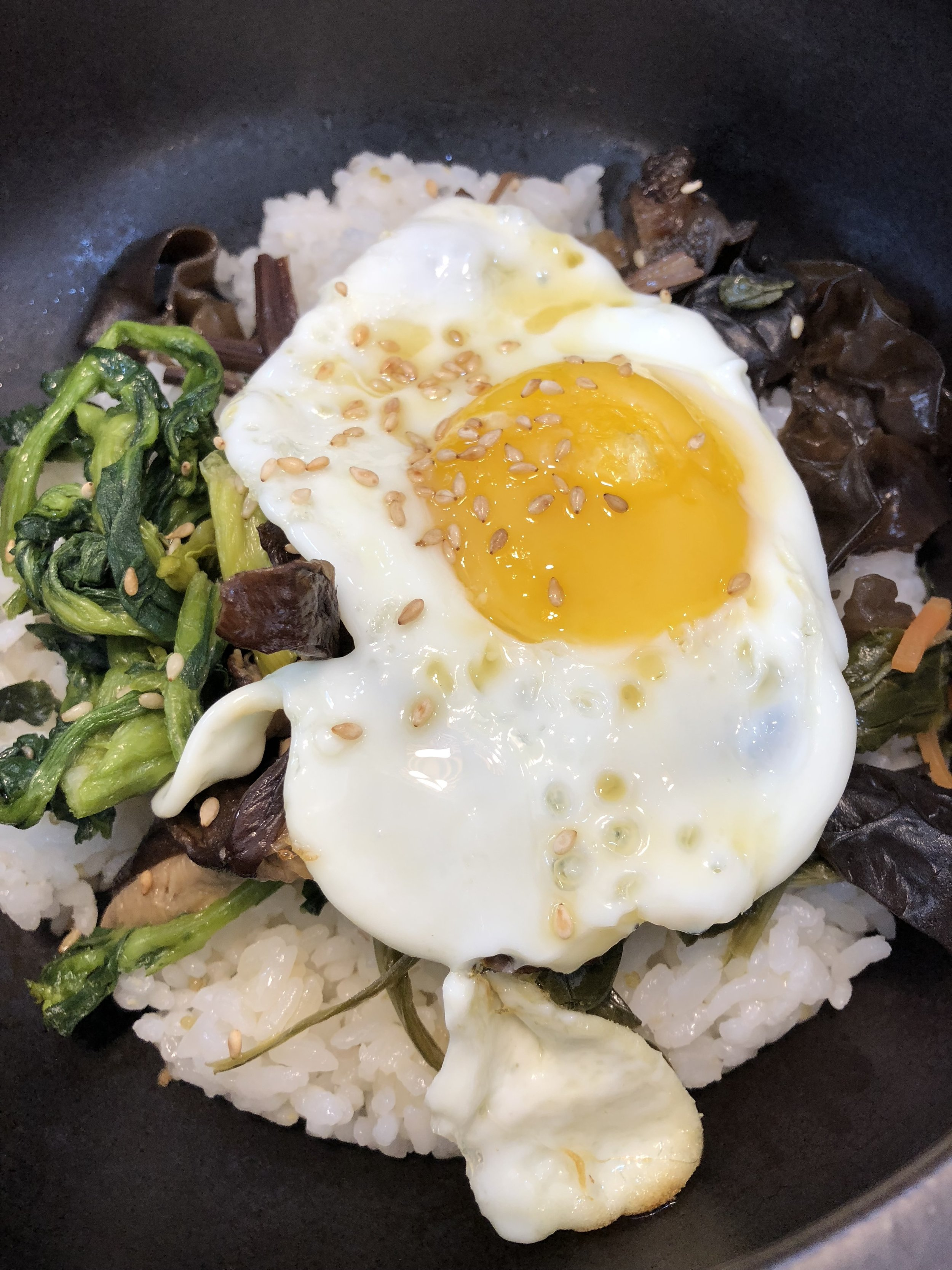 Delicious bibimbap — rice, herbs, egg, and veg served in a sizzling hot bowl. Mix with red pepper paste and enjoy!