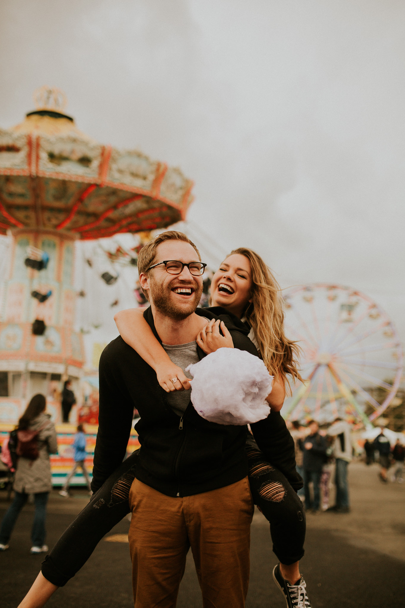 moody warm state fair engagement photography with cotton candy.